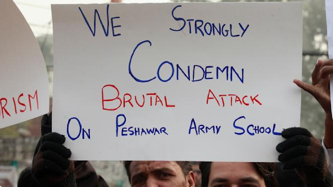 Member of the civil society hold placard and chant slogans to condemn attack on the Army Public School by Pakistan Taliban gunmen, during a rally with others in Lahore