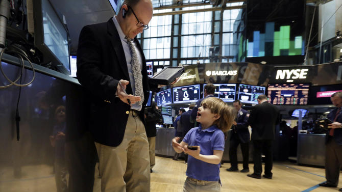 Tripp Mancuso, 4, works with his trader father Peter Mancuso on the floor of the New York Stock Exchange, during the NYSE Working Parents/Caregivers Employee Resource Group's annual Take Your Child to Work Day program, Thursday, April 24, 2014. Mixed earnings from a large number of U.S. companies left the stock market without direction early Thursday, despite positive results from a handful of names including Apple and Caterpillar. (AP Photo/Richard Drew)