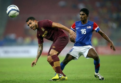 Manchester City's player Carlos Tevez (L) shields the ball from Malaysia's player S. Kunanlan