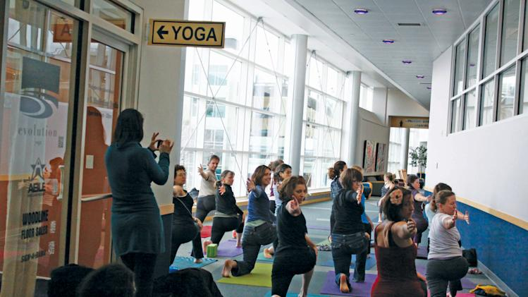 This Jan. 12, 2013 photo released by Burlington International Airport shows a local class doing yoga at the Burlington International Airport in Burlington, Vt., to celebrate the grand opening of a yoga space for travelers.  The airport is one of at least three airports offering a space for travelers to practice yoga while waiting for flights to make their trip more relaxing. (AP Photo/Burlington International Airport)