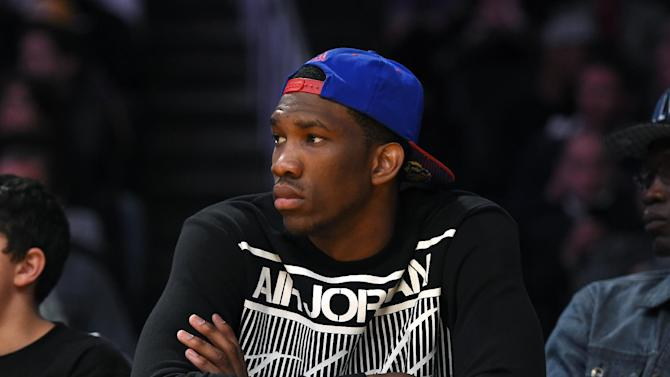 Kansas center Joel Embiid watches the Los Angeles Lakers play the Memphis Grizzlies in an NBA basketball game, Sunday, April 13, 2014, in Los Angeles. The Grizzlies won 102-90
