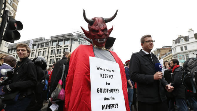 A masked demonstratorq holds a banner along the ceremonial funeral procession route of former British Prime Minister Margaret Thatcher, central London, Wednesday, April 17, 2013. A coffin containing the body of former Prime Minister Margaret Thatcher was driven Wednesday from the Houses of Parliament to the church of St. Clement Danes for prayers ahead of the former leader's full funeral at St. Paul's Cathedral. (AP Photo/Lefteris Pitarakis)