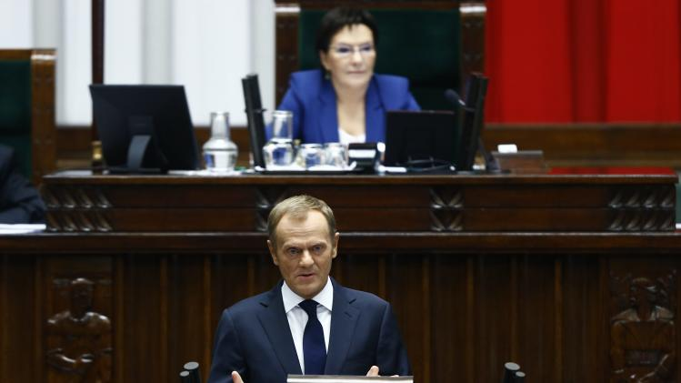 Poland's Prime Minister Donald Tusk delivers a speech in front of speaker of parliament, Ewa Kopacz, at parliament in Warsaw