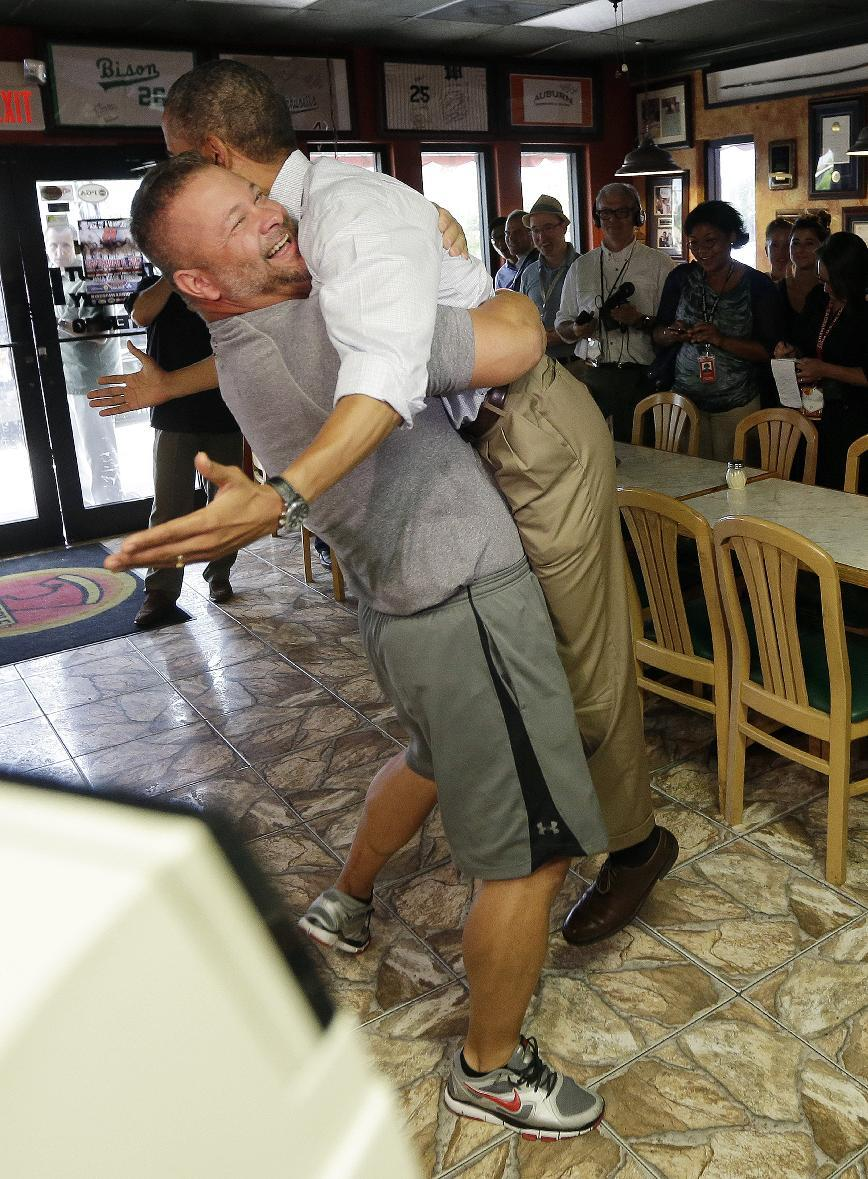 President Barack Obama, right, is picked-up and lifted off the ground by Scott Van Duzer, left, owner of Big Apple Pizza and Pasta Italian Restaurant, during an unannounced stop, Sunday, Sept. 9, 2012, in Ft. Pierce, Fla. (AP Photo/Pablo Martinez Monsivais)
