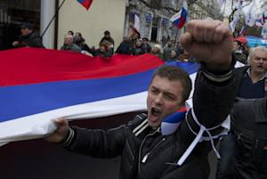 Local residents carry Russian flags and shout slogans …