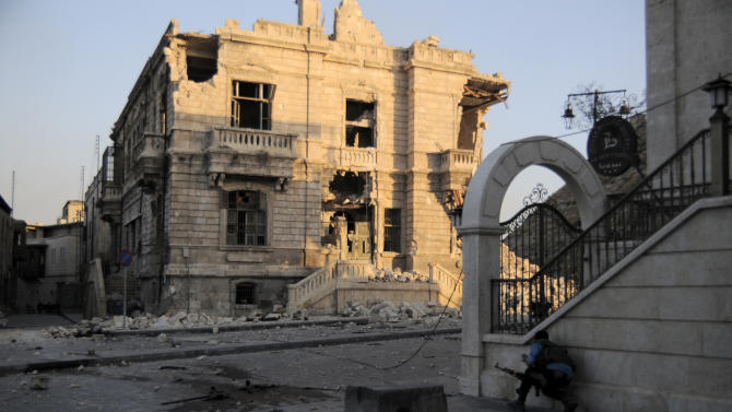 In this Tuesday, Nov. 6, 2012 photo, a Syrian rebel fighter takes cover a few meters away from the Castle, used as a military position by Bashar Assad's forces in the Old City of Aleppo, Syria.(AP Photo/Monica Prieto)