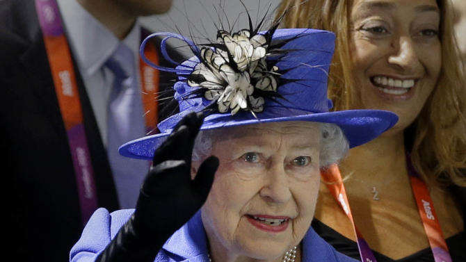 Britain's Queen Elizabeth II waves to spectators inside the Aquatics center during a visit to the Olympic Park at the 2012 Summer Olympics, Saturday, July 28, 2012, in London. (AP Photo/Ben Curtis)