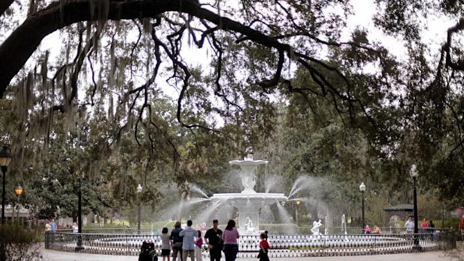 In this Feb. 21, 2011 photo, people gather at the Forsythe Park fountain in the historic district of Savannah, Ga. A proposal to roll out double-decker buses on the streets of historic downtown Savannah has residents complaining the change would amount to a tourism overload. Two Boston businessmen are lobbying Savannah City Hall to end a 17-year ban on double-decker buses in the downtown historic district of Georgia's oldest city. The city's Downtown Neighborhood Association is opposing the change. Its members say the buses would risk collisions with low-hanging tree limbs and would turn passengers into Peeping Toms capable of peering into second-story windows. (AP Photo/David Goldman)