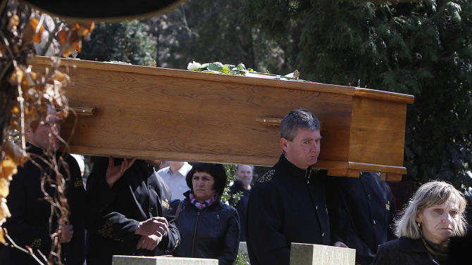 Pallbearers carrying the wooden casket of Barbara Piasecka Johnson to her burial site at a cemetery in Wroclaw, Poland, on Monday, April 15, 2013. . A farmer's daughter, she came to The United State in 1968 and worked as a maid for an American heir to the Johnson & Johnson fortune before marrying him and eventually inheriting some $300 million of his wealth. An art collector and philanthropist, she died near Wroclaw on April 1. (AP Photo/Czarek Sokolowski)