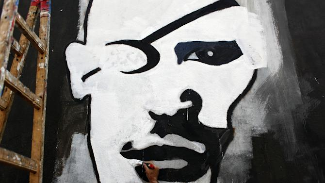 """FILE - In this Sunday. Sept. 30, 2012 file photo, an Egyptian activist artist works on a mural depicting a rebel with an eye patch in Tahrir square, Cairo, Egypt. Graffiti has been among the most powerful art forms and tools of Egypt's revolution and the turbulent months since, but it also has proven to be its most vulnerable and ephemeral. So a group of artists, photographers and a publisher joined hands to preserve the images. """"Wall Talk"""" _ their newly released, 680-page book _ collects hundreds of photos of graffiti dating from the Jan. 25, 2011 eruption of the revolt against then-President Hosni Mubarak until today. (AP Photo/Nasser Nasser, File)"""