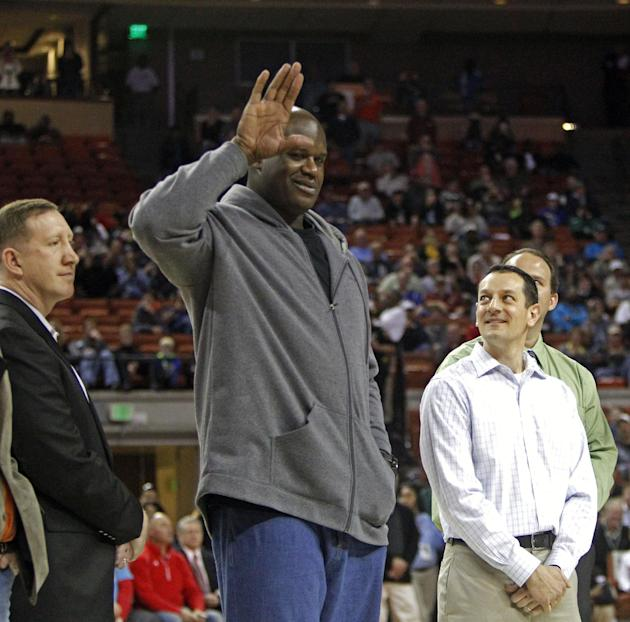 Former NBA star Shaquille O'Neal waves to the crowd while standing with his former high school teammates during halftime of the boys' UIL Class 1A Division 1 state basketball final, Saturday,