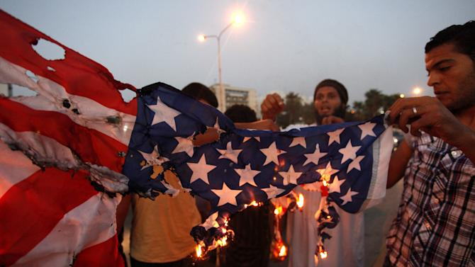 """FILE - In this Friday, Sept. 14, 2012, photo, Libyan followers of Ansar al-Shariah Brigades burn the U.S. flag during a protest in front of the Tibesti Hotel, in Benghazi, Libya, as part of widespread anger across the Muslim world about a film ridiculing Islam's Prophet Muhammad. Ansar al-Shariah is among the most powerful of the heavily armed militias that the government relies on to keep security in Benghazi. Suspicion in last week's deadly attack that killed the American ambassador to Libya has focused on members of a hardcore Islamist militia known for its sympathies to al-Qaida, its fierce animosity to the U.S. and its intimidation of Muslims who don't conform to its strident ideology. Around 150 members of Ansar al-Shariah Brigades chanted """" Obama, Obama, we are all Osama."""" (AP Photo / Mohammad Hannon, File)"""