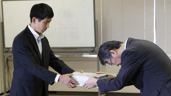 Nuclear Regulation Authority (NRA)'s head of coordination group emergency response Tomoya Ichimura, left, receives application documents from Hokkaido Electric Power Co. Inc. Vice President Osamu Sakai in Tokyo, Monday, July 8, 2013. Four of nine Japanese nuclear plant operators - supplying the regions of Hokkaido, Kansai, Shikoku and Kyushu - filed applications for safety inspections by the NRA for 10 reactors at five plants Monday, when new safety requirements take effect. Japan moved a step closer to restarting nuclear reactors Monday as four utility companies applied for inspections at 10 of their idled reactors, the clearest sign of a return to nuclear energy nearly two and a half years after the Fukushima disaster. (AP Photo/Koji Sasahara)