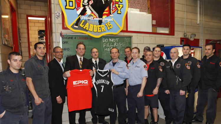 IMAGE DISTRIBUTED FOR EPIQ - Director of Brand Management Sports Nutrition for EPIQ Brent Coward, Vice President of GNC Vincent Cacace, FDNY Chief John Bley, FDNY Captain David Drake, FDNY Lt. James Amsterdam (center) and the FDNY of Engine 4, Ladder 15 pose for a photo at EPIQ Thank You In Relief of Sandy on Tuesday, Feb. 5, 2013 in New York City. (Photo by Amy Sussman/Invision for EPIQ/AP Images)