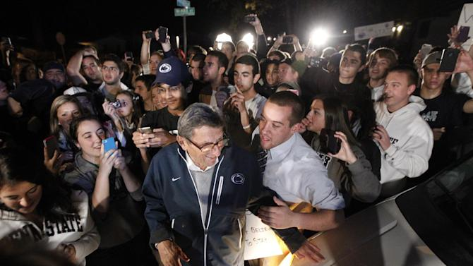 "Students greet Penn State football coach Joe Paterno as he arrives at his home, Tuesday, Nov. 8, 2011, in State College, Pa. Paterno's support among the Penn State board of trustees was described as ""eroding"" Tuesday, threatening to end the 84-year-old coach's career amid a child sex-abuse scandal involving a former assistant and one-time heir apparent. (AP Photo/Matt Rourke)"