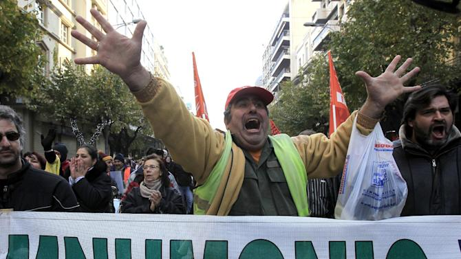 "Striking Greek municipal employees chant slogans during a protest outside at the northern port city of Thessaloniki, Greece as a banner reads in Greek ""bailout agreement"" Friday, Dec. 14, 2012.  Greek municipal workers demonstrated against government plans to suspend 2,000 civil servants for potential dismissal due to state budget cuts. AP Photo/Nikolas Giakoumidis)"