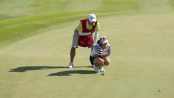 Sei Young Kim, right, of South Korea, looks over the 17th green with the help of her caddie in the third round of the LPGA Lotte Championship golf tournament Friday, April 17, 2015, in Kapolei, Hawaii. (AP Photo/Eugene Tanner)