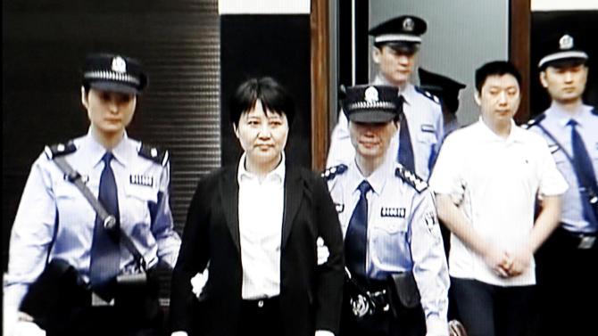 FILE - In this Aug. 9, 2012 file video image taken from CCTV, Gu Kailai, second left, the wife of disgraced politician Bo Xilai, is taken to her trial in the Hefei Intermediate People's Court in Hefei in eastern China's Anhui province.  Gu was given a suspended death sentence Monday, Aug. 20, 2012,  after confessing to killing a British businessman in a case that rocked the country's top political leadership.  A man in white shirt at right is Zhang Xiaojun, family aide of Gu.  (AP Photo/CCTV via APTN, File) CHINA OUT, TV OUT