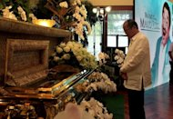 Philippine President Benigno Aquino offers prayers next to the casket of the late Rodolfo Vera Quizon, popularly known as Dolphy, during a visit to the wake at a funeral parlor in Manila on July 12. The Philippines' top film and television actors and leading politicians joined hundreds of relatives and friends of the country's most popular comedian as his body was laid to rest Sunday