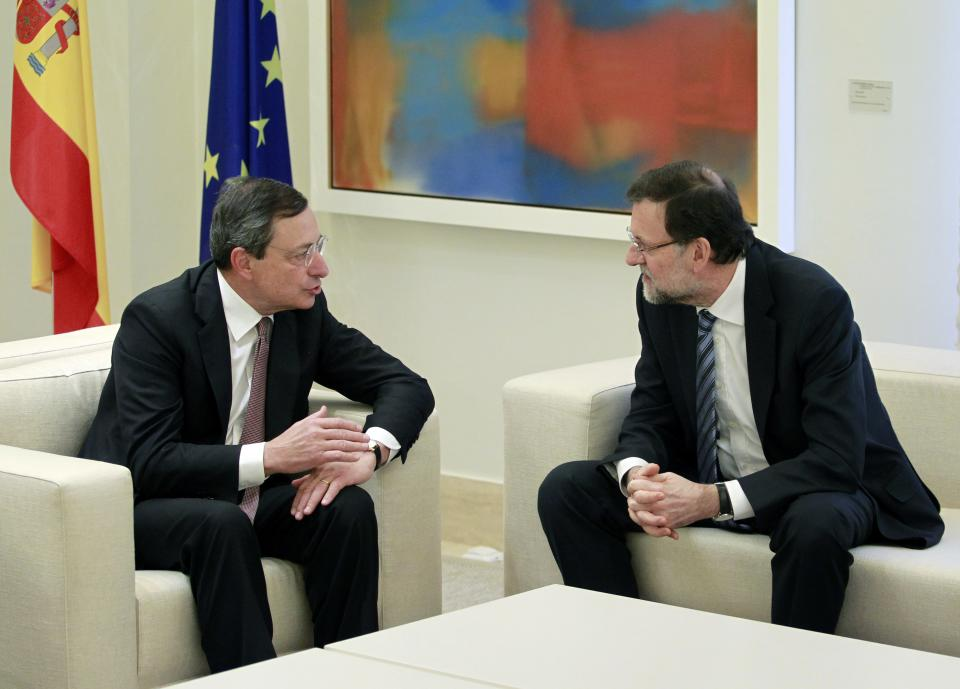 President of the European Central Bank Mario Draghi, left, speaks to Spain's Prime Minister Mariano Rajoy, right, during a meeting at the Moncloa Palace, in Madrid, Spain, Tuesday, Feb. 12, 2013. (AP Photo/Andres Kudacki)