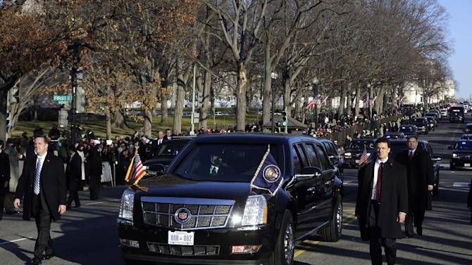 President Barack Obama and first lady Michelle Obama ride in the presidential limousine during the 57th Presidential Inauguration parade Monday, Jan. 21, 2013, in Washington. (AP Photo/Charles Dharapak)