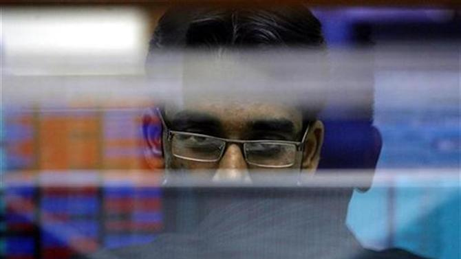A broker looks at a terminal while trading at a stock brokerage firm in Mumbai