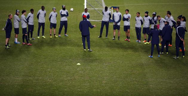 Paris St Germain's coach Laurent Blanc speaks with his players during a training session in Lisbon