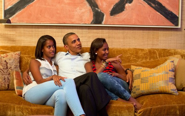 In this handout photo provided by The White House, U.S. President Barack Obama and his daughters, Malia (L) and Sasha, watch on television as first lady Michelle Obama takes the stage to deliver her s