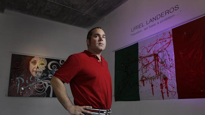 """In this  Oct. 23, 2012 photo, James Perez, owner of Cueto James Art Gallery, poses between pieces titled """"Ego"""", left, and """"Legalize Drugs"""", right, that will be in the show titled """"Uriel Landeros: Houston We Have a Problem"""" in Houston. Landeros, accused of vandalizing a 1929 Pablo Picasso painting at the museum, was ordered jailed on bonds totaling $500,000 Wednesday, Jan. 16, 2013 after a Houston  judge said he is a flight risk.  Landeros fled Texas after spray painting the Picasso, an act caught on cellphone video, and surrendered to authorities last week at the U.S.-Mexico border. (AP Photo/Houston Chronicle, Melissa Phillip, File) MANDATORY CREDIT"""