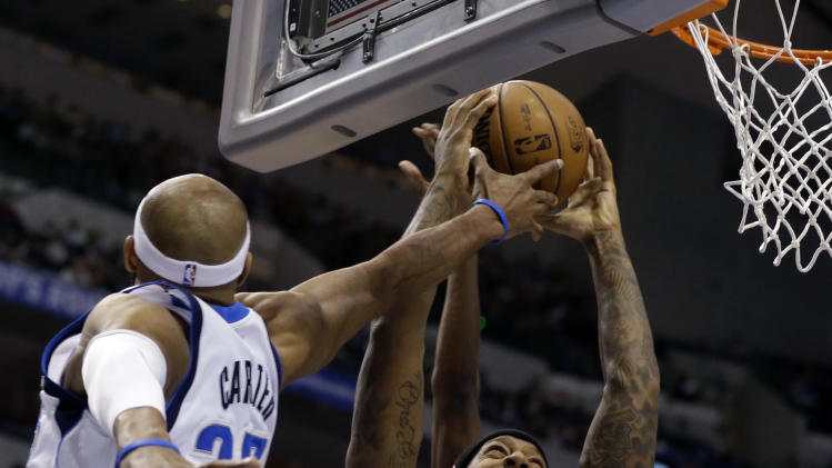 Dallas Mavericks' Vince Carter (25) tries to block Sacramento Kings' James Johnson (52) as he goes up to score in the first half of an NBA basketball game as the Mavericks' Dirk Nowitzki, bottom right, of Germany watches Wednesday, Feb. 13, 2013, in Dallas. (AP Photo/Tony Gutierrez)