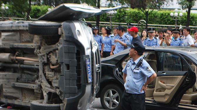 In this Aug. 19, 2012 photo, a police officer looks at Japanese-made cars attacked by anti-Japan demonstrators in Shenzhen in Guangdong Province, China. Sales of Toyota and Honda vehicles nosedived in China during September as anti-Japanese sentiment flared over a territorial dispute that threatens to hobble what was a booming business relationship between Japan and its biggest export market. Toyota Motor Corp. said Tuesday, Oct. 9, that sales of new vehicles in China dropped 48.9 percent in September from a year earlier to 44,100 vehicles. Honda Motor Co. said September sales plunged 40.5 percent to 33,931 vehicles. China sales for Nissan Motor Co. slid 35.3 percent last month to 76,100 vehicles. (AP Photo/Kyodo News) JAPAN OUT, MANDATORY CREDIT, NO LICENSING IN CHINA, FRANCE, HONG KONG, JAPAN AND SOUTH KOREA