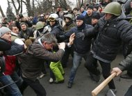 Anti-government protesters attack a deputy of the Party of Regions Vitaly Grushevsky (2nd L, front) outside the Ukrainian Parliament building in Kiev February 22, 2014. REUTERS/Vasily Fedosenko