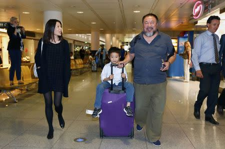 Dissident Chinese artist Ai Weiwei with his son Ai Lao leave the airport in Munich