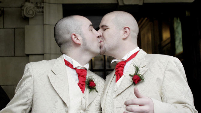 FILE- In this Monday, Dec. 19, 2005 file photo, Henry Edmont Cane, left,  and partner Christopher Patrick Flanaghan  kiss outisde Belfast, City Hall, Belfast, Northern Ireland, Monday, Dec. 19, 2005.  The couple became the first male couple to  win legal recognition for their partnership under a new  British civil partnership law.  Prime Minister David Cameron and senior British officials threw their weight behind gay marriage Tuesday, Feb. 5, 2013,  reiterating their support of a proposed bill hours ahead of a key Parliament vote on the divisive topic.  (AP Photo/Peter Morrison, File)