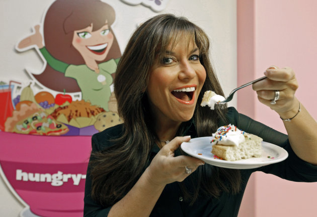 "In this Oct. 11, 2012 photo, ""Hungry Girl"" Lisa Lillien poses in her office in the Woodland Hills area of Los Angeles. She never set out to become a controverisal food maven, telling people how to eat their cake and keep their weight down too. Lillien was just another LA ""Hungry Girl,"" a 30-something woman who would diet off that extra 20 pounds and then put the weight back on. That was until the former studio publicist started coming up with low-cal recipes for some of those favored foods and emailing them around to friends. Ten years later, Lillien sits atop a Hungry Girl empire. ( AP Photo/Nick Ut)"