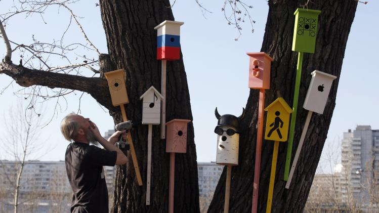 "Russian artist Vasily Slonov stands near a tree after attaching wooden starling houses during a presentation of his artwork called ""Total Spring"" on an island in the middle of the Yenisei River in Krasnoyarsk"