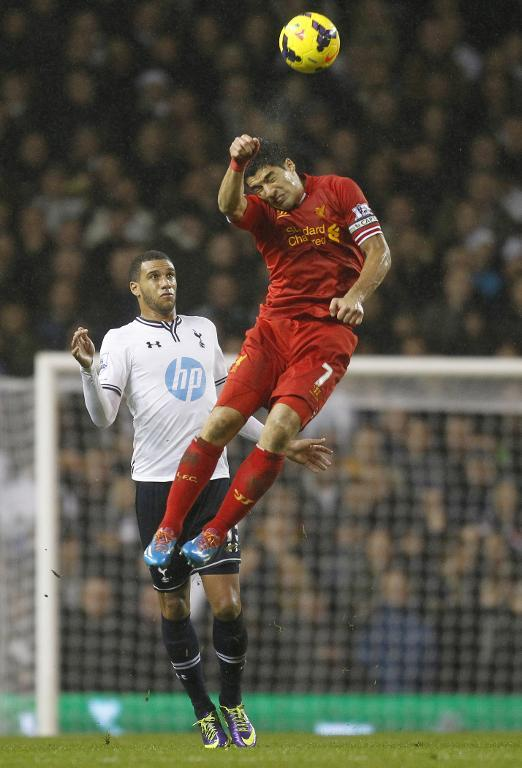 Luis Suarez outjumps Tottenham's Etienne Capoue during a Premier League game at White Hart Lane in London on December 15, 2013