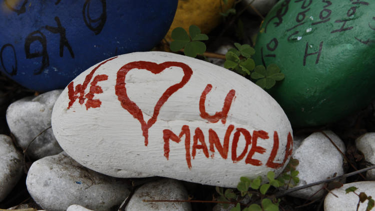 A pebble with a message to former President Nelson Mandela lays outside his Johannesburg home Thursday, Dec. 27 2012. Mandela was released Wednesday from the hospital after being treated for a lung infection and having gallstones removed, a government spokesman said. (AP Photo/Denis farrell)