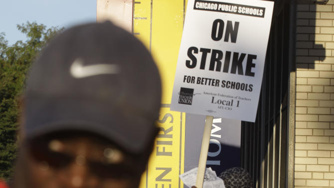 Chicago teachers walk a picket line outside Benjamin Banneker Elementary School in Chicago, early Monday, Sept. 10, 2012, after they went on strike for the first time in 25 years. Union and district officials failed to reach a contract agreement despite intense weekend negotiations. (AP Photo/M. Spencer Green)