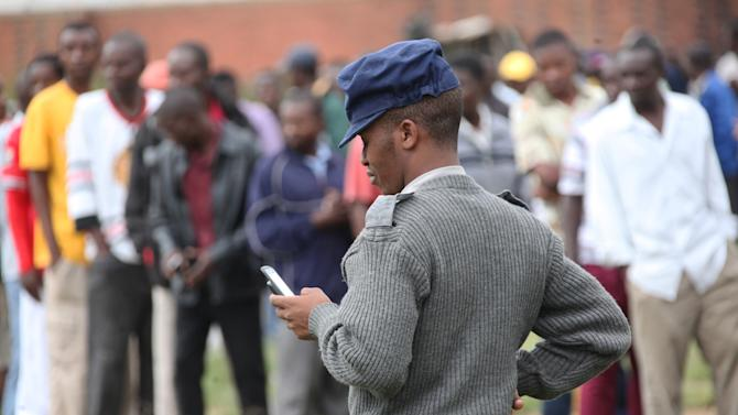 A police officer chats on a mobile phone at a polling station during a referendum in Harare, Zimbabwe, Saturday, March, 16, 2013. All political groups have called for a 'Yes' vote on a constitution whose reforms would reduce presidential powers and grant more democratic rights. However, even if the constitution is approved, arrests and harassment of rights and democracy activists this year by police loyal to Mugabe raise doubts about whether such changes would be seriously enforced. (AP Photo/Tsvangirayi Mukwazhi)