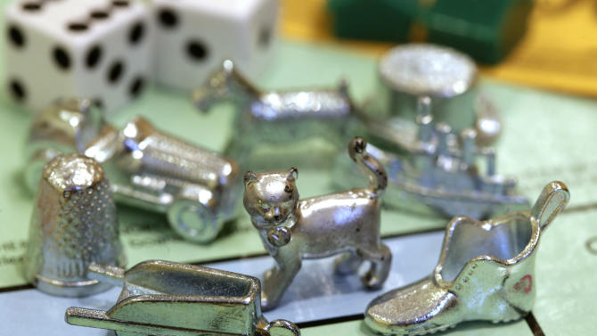 The newest Monopoly token, a cat, center, rests on a Boardwalk deed next to other tokens still in use including the wheelbarrow, left, and the shoe, right, at Hasbro Inc. headquarters, in Pawtucket, R.I., Tuesday, Feb. 5, 2013.  Voting on Facebook determined that the cat would replace the iron token.  (AP Photo/Steven Senne)