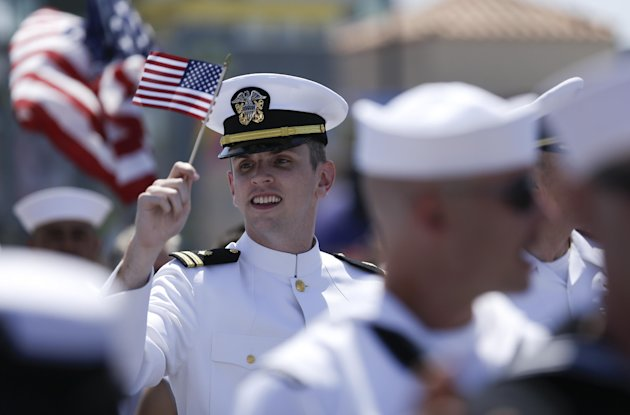 A sailor waves a flag during the gay pride parade Saturday, July 21, 2012, in San Diego. For the first time ever, U.S. service members marched in a gay pride event decked out in uniform Saturday, afte
