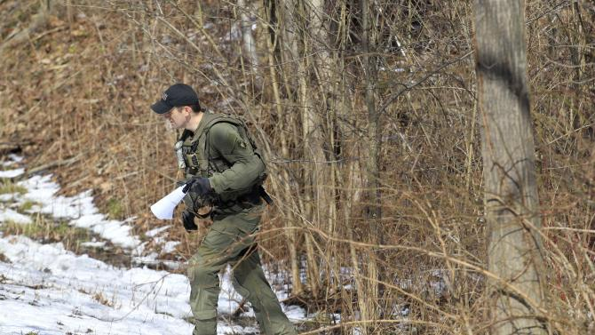 An FBI agent searches a wooded several miles from the shooting Monday, Feb. 27, 2012, in Chardon, Ohio. A gunman opened fire inside a high school cafeteria at the start of the school day Monday, killing one student and wounding four others, authorities said. A suspect believed to be a student was arrested a short distance away. (AP Photo/Tony Dejak)