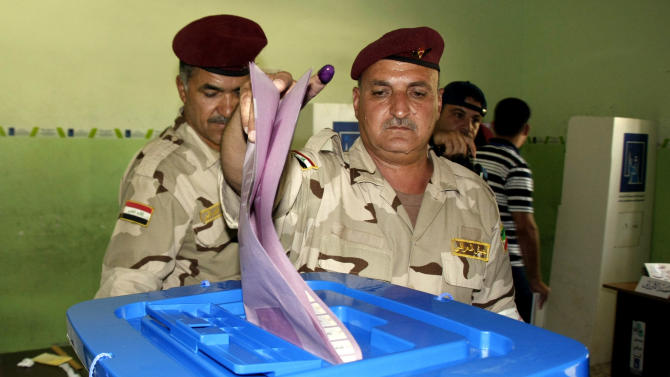 An Iraqi soldier casts his vote at a polling center during early voting for security forces in the country's provincial elections in Mosul, 225 miles (360 kilometers) northwest of Baghdad, Iraq, Monday, June 17, 2013. In the western town of Fallujah, a suicide bomber set off explosives among a group of policemen, killing several and wounding more than a dozen. The policemen were waiting for buses to take them to a polling station to cast their ballots for Iraq's provincial elections. (AP Photo)