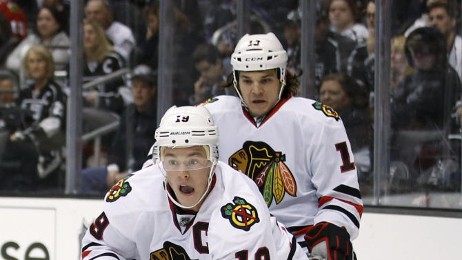 Chicago Blackhawks' Jonathan Toews(19) controls the puck past Los Angeles Kings' Drew Doughty(8) as Blackhawks' Daniel Carcillo watches during the first period of an NHL hockey game in Los Angeles, Saturday, Jan. 19, 2013. (AP Photo/Jae C. Hong)