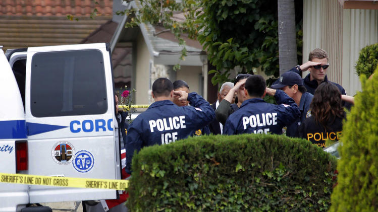 Immigration and Customs Enforcement (ICE) agents lining the driveway of a home in Carson, Calif. salute as the body of an ICE agent covered by an American flag is wheeled to a coroner's van on Thursday, May 3, 2012. The 14-year-old son of a federal agent was arrested Thursday in the shooting death of his father in their Southern California home, authorities said.    (AP Photo/Nick Ut)