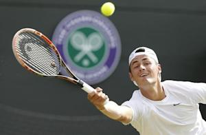 Bernard Tomic of Australia hits a return to Tomas Berdych of Czech Republic during their men's singles tennis match at the Wimbledon Tennis Championships, in London