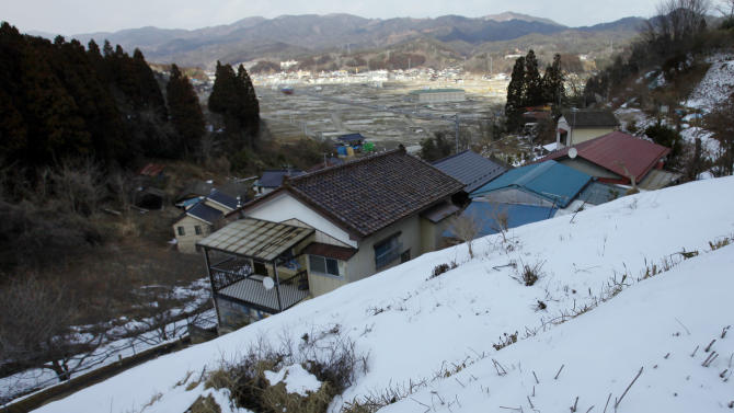 In this Thursday, Feb. 21, 2013 photo, an area devastated by the March 11, 2011 earth quake and tsunami is seen from a higher place in Kesennuma, Miyagi Prefecture. Japan's progress in rebuilding from the tsunami that thundered over coastal sea walls, sweeping entire communities away, is mainly measured in barren foundations and empty spaces. Clearing of forests on higher ground due to be leveled to make space for relocating survivors has barely begun. Japan will next week observes two years from the March 11, 2011 disasters which devastated in the northeastern Pacific coast of the country. (AP Photo/Junji Kurokawa)