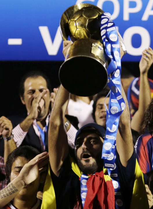 Guiza of Cerro Porteno celebrates with the trophy after defeating Nacional during their Paraguay Primera Division match to win the championship in Asuncion
