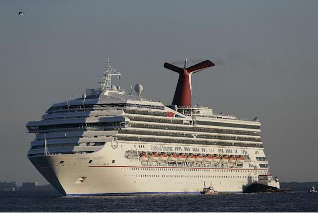 FILE - In this Feb. 14, 2013 file photo the cruise ship Carnival Triumph is towed into Mobile Bay near Dauphin Island, Ala. The Triumph, which has been docked in Alabama since an engine room fire left